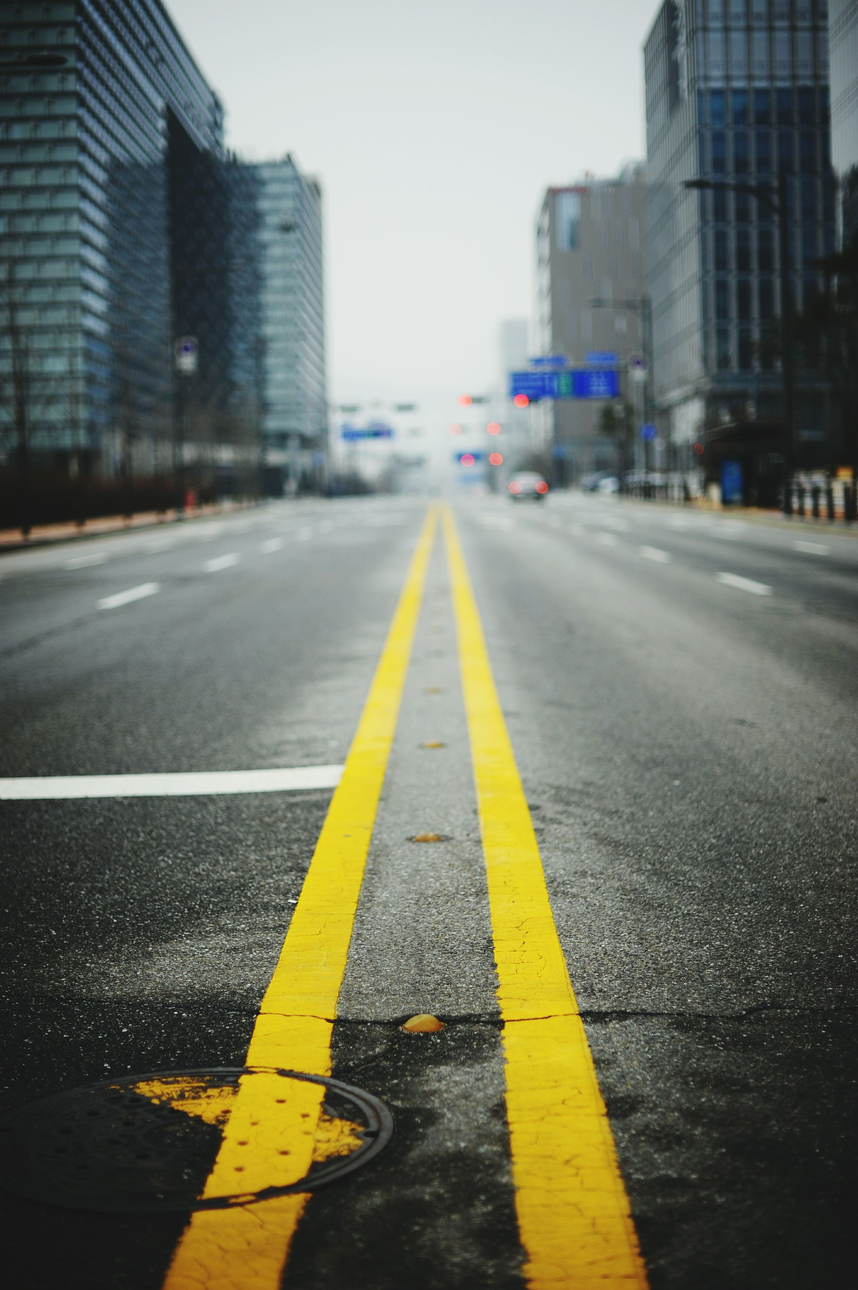 the way forward, road marking, transportation, building exterior, diminishing perspective, architecture, built structure, city, road, street, vanishing point, asphalt, yellow, surface level, arrow symbol, city life, dividing line, outdoors, sky, road sign