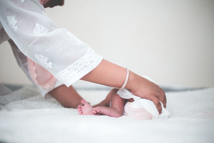 Close-Up Of Mother Adjusting Daughter On Bed
