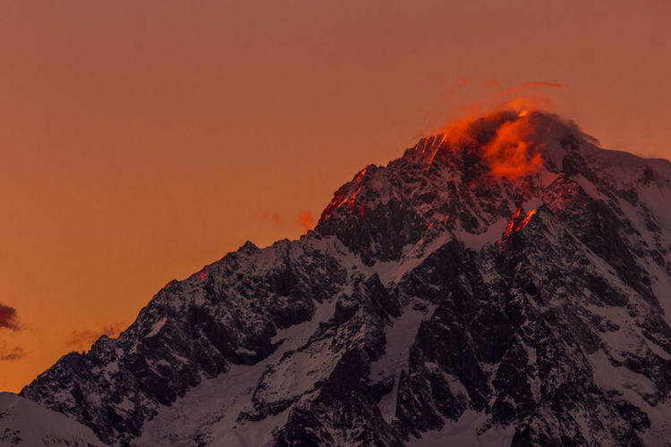 Scenic View Of Snowcapped Mountains Against Orange Sky