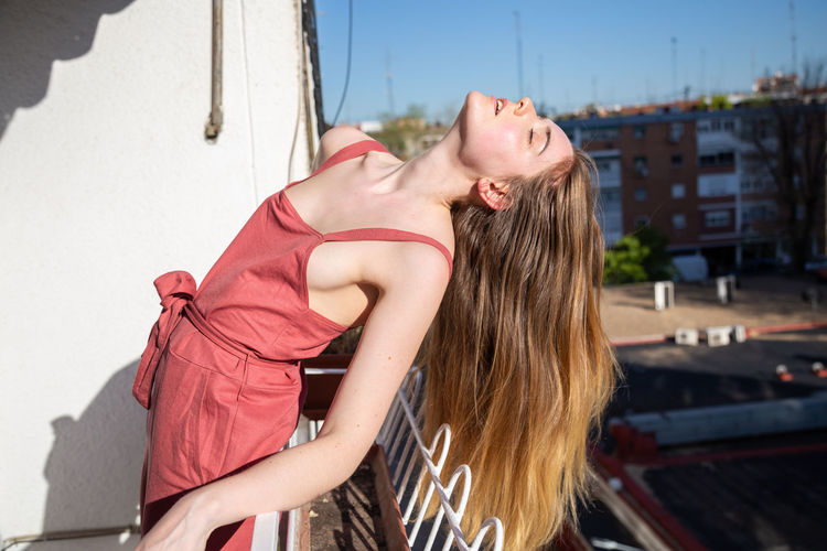 Portrait of young attractive woman in casual summer dress leaning on railing of balcony Girl Copy Space Woman Balcony Relaxing Posing Leaning Railing Terrace Summer Young Adult Female Beautiful Attractive Pretty Charming Sensual 💕 Elegant Cool Casual Dress Seductive Gorgeous Appealing Standing Posture Model Resting Recreation  Relaxation Sunny Blue Sky Heaven Urban Sunlight City Street Plants Pots Home Indoors  Blurred Background Long Hair