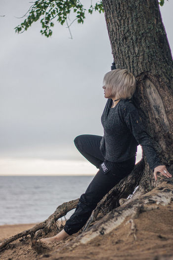 Woman sitting on tree trunk against sky