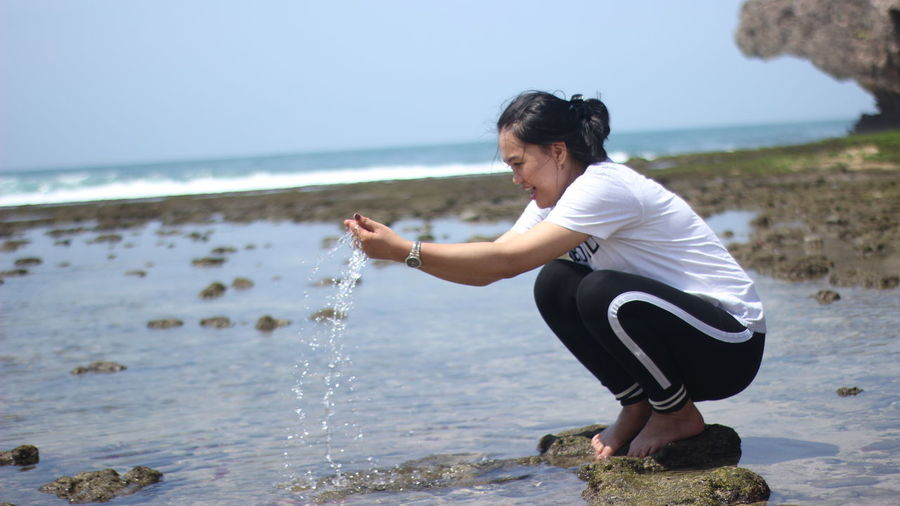 Full length of woman playing with water at beach