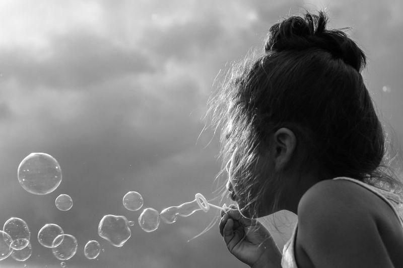 Fun Monochrome Black And White Blowing Bubbles One Person Real People Headshot Lifestyles Women Leisure Activity Portrait Bubble Fragility Child Vulnerability  Outdoors Hairstyle Girls Day Hair Moments Of Happiness