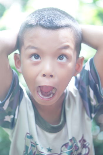 Close-up of boy making face outdoors
