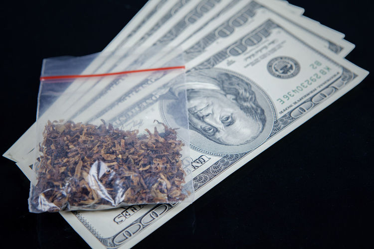 Close-up of marijuana on paper currency over black background