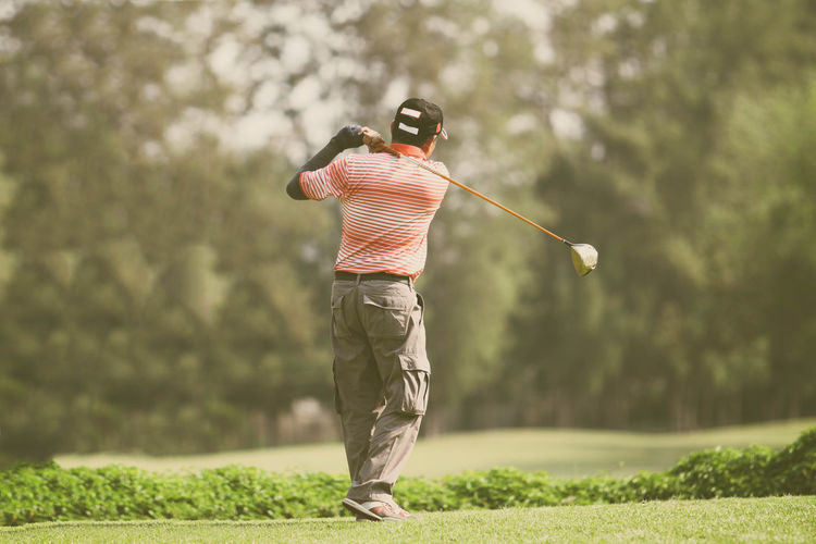 Ball Casual Clothing Day Focus On Foreground Full Length Golf Golf Club Golf Course Golf Swing Golfer Grass Leisure Activity Lifestyles Men Motion One Person Outdoors Real People Rear View Recreational Pursuit Skill  Sport Standing Taking A Shot - Sport Tree