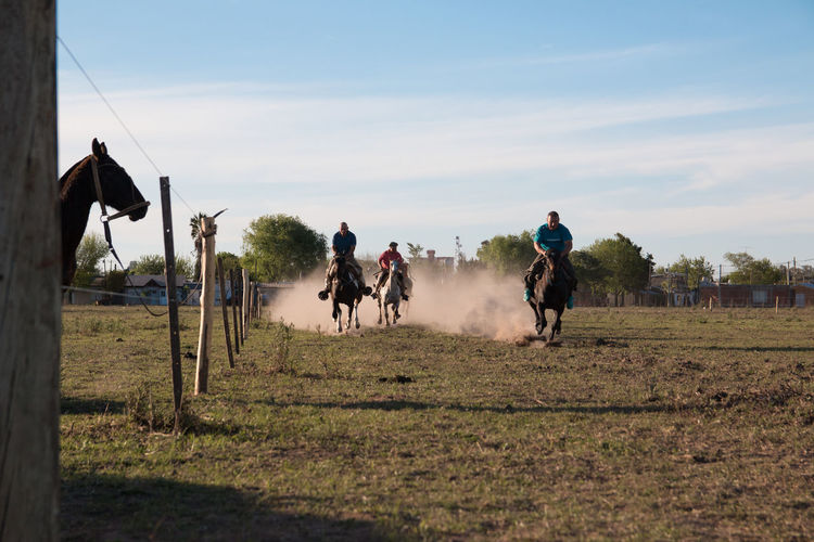 People riding horses on field against sky