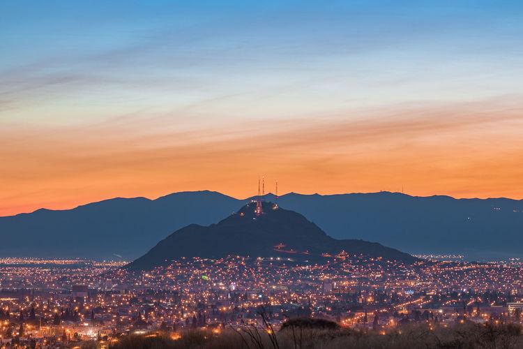 Illuminated cityscape against sky at sunrise