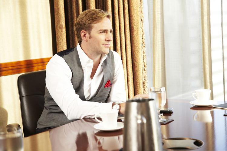 Cool Confidence. Young elegant businessman sitting in conference room smirking. Businessman Business Business Meeting Serious Looking Portrait Confidence  Attitude Elégance Beautiful People Handsome Conference Room Board Room One Man Only Caucasian Ethnicity Staring Corporate Business Businesswear Young Adult Lifestyles Arms Crossed Cool Attitude Masculinity Fashionable Successful The Modern Professional