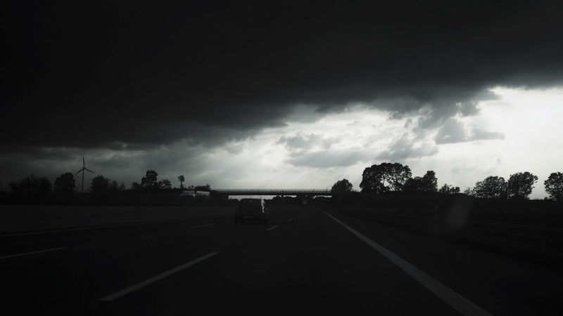 hold on Black Background Blackandwhite Car Cloud - Sky Day Driving Germany Highway IPhoneography Light Light And Shadow Monochrome No People Outdoors Pin Wheel Road Sky Storm Cloud The Way Forward Transportation Tree Wind Power Wind Turbine