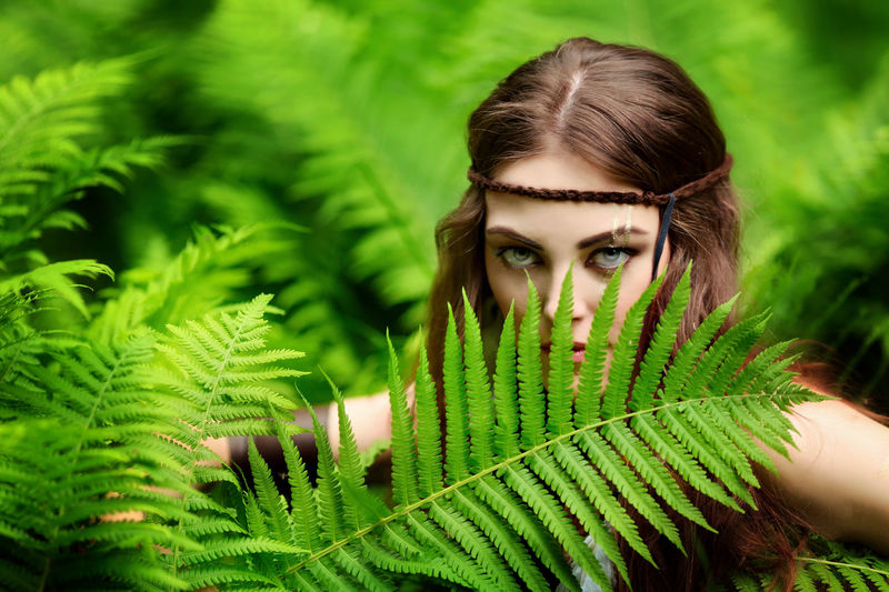 Portrait of young woman with plants fern