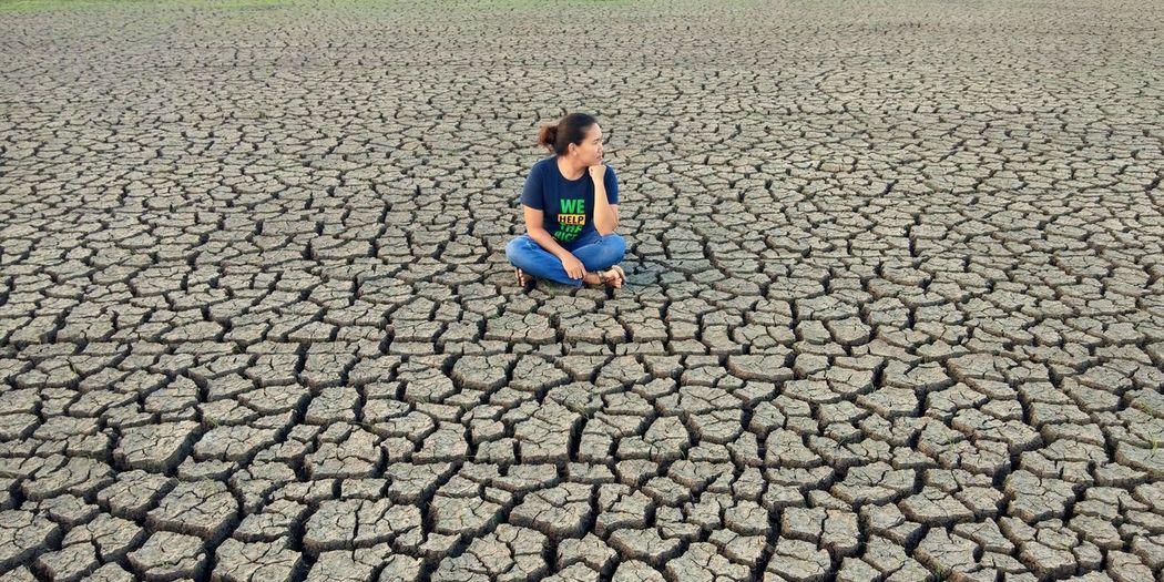 Full Length Of Woman Sitting On Barren Landscape