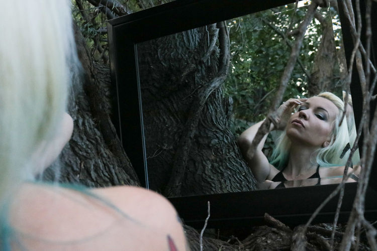 Young beautiful woman looking in mirror against tree branches in forest