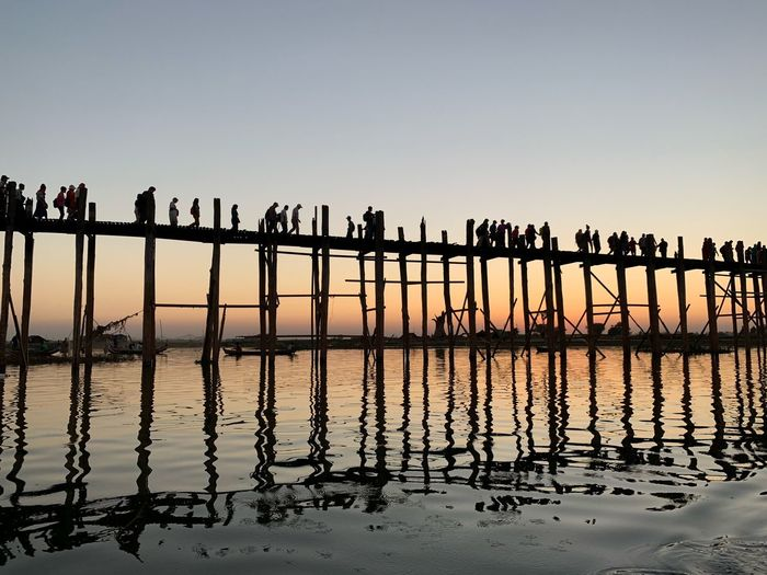 Silhouette people on bridge over sea against sky during sunset