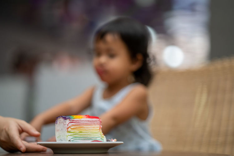 Rear view of little girl looking at table
