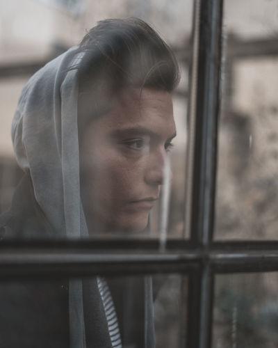 Sad man seen through glass window