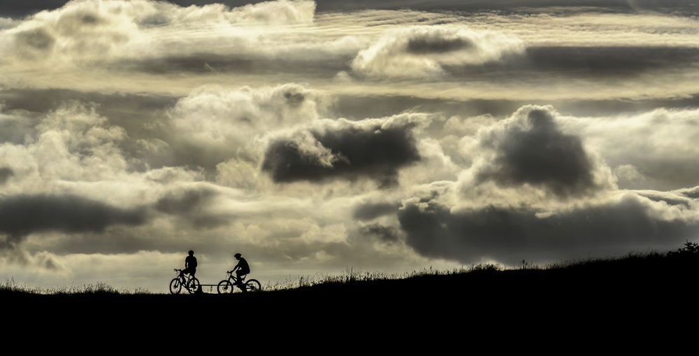 Mountain bikers on the Malvern Hills, Worcestershire, UK Malvern Hills Beauty In Nature Bonding Child Cloud - Sky Field Land Leisure Activity Lifestyles Love Men Mountain Biking Nature Outdoors People Positive Emotion Real People Scenics - Nature Silhouette Sky Sunset Togetherness Tranquility Two People