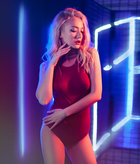 Fashion art photo of elegant blonde model in seductive wear with light neon colored club spotlights Beautiful Woman Beauty Blond Hair Disco Dancing Fashion Front View Hair Hairstyle Illuminated Indoors  Long Hair Night Nightlife One Person Stage Standing Three Quarter Length Women Young Adult Young Women