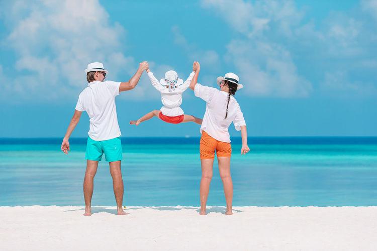 Full length of women standing at beach against sky