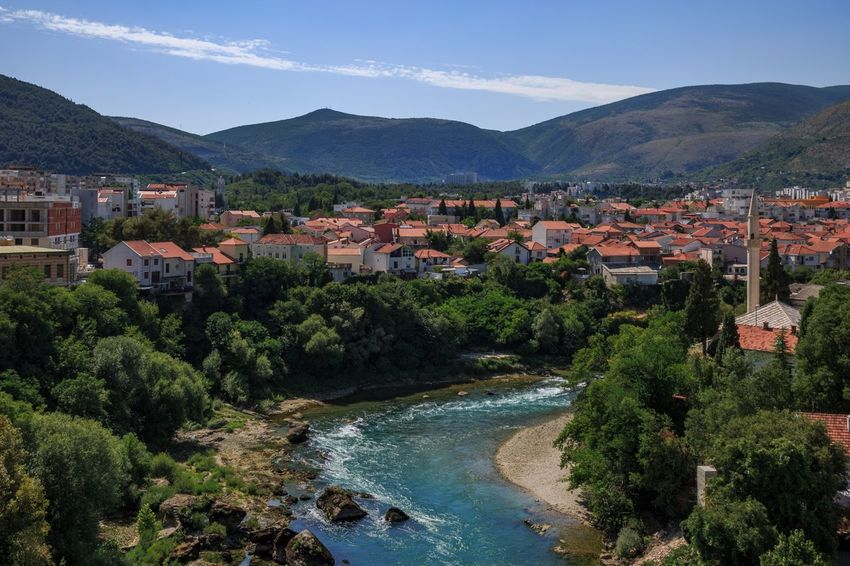 Old town Mostar Bosnia And Herzegovina Mostar Mountain Built Structure Architecture Building Exterior House Mountain Range River Town Outdoors Water Day Beauty In Nature Tree Sky No People High Angle View Nature Community Residential Building Scenics