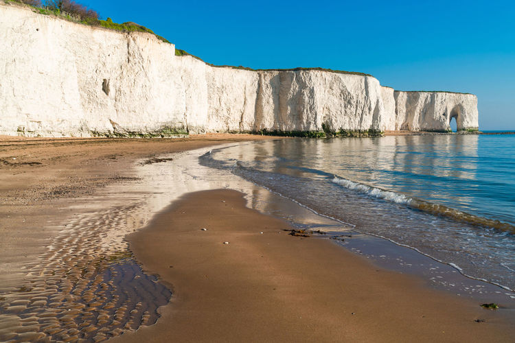 View of white chalk cliffs and beach in Kingsgate Bay, Margate, East Kent, UK Chalk Cliffs Bay Beach Beauty In Nature Blue Clear Sky Cliff Day Kingsgate Bay Land Nature No People Non-urban Scene Outdoors Rock Sand Scenics - Nature Sea Sky Sunlight Tranquil Scene Tranquility Water White