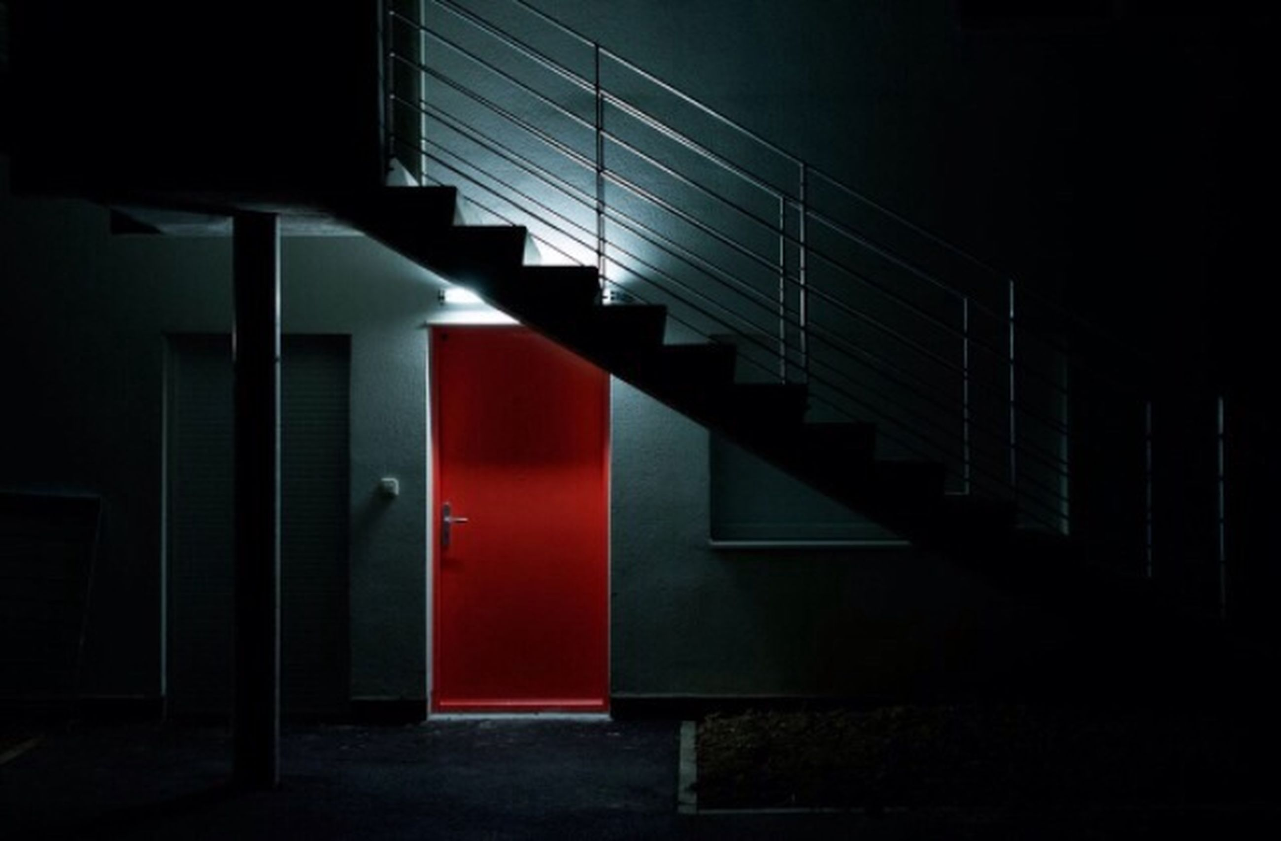 indoors, red, architecture, built structure, steps, railing, staircase, in a row, no people, empty, absence, steps and staircases, illuminated, window, wall - building feature, building, modern, wall, shadow, sunlight