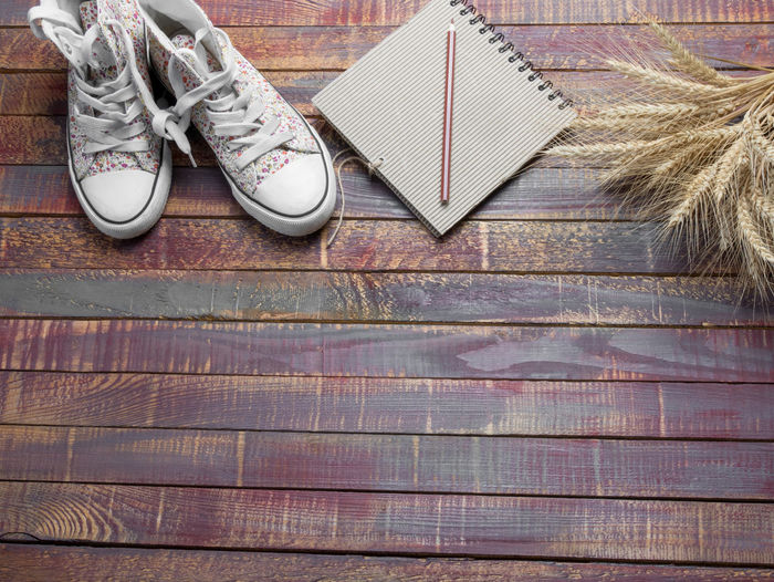 Close-up of shoes and spiral notebook with cereal plants on wooden table