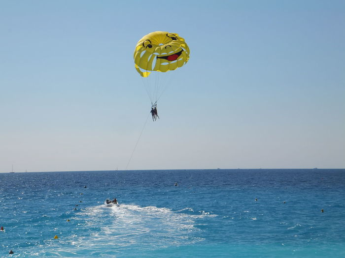 Smiley Face Parachute Over Sea Against Clear Sky