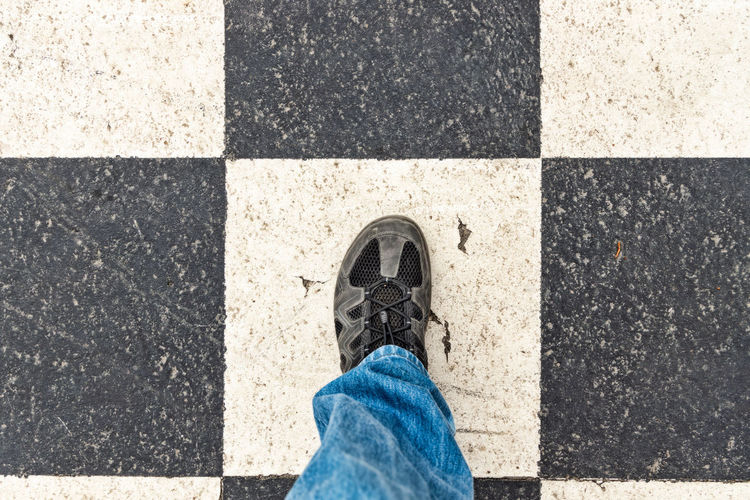 person on large chessboard outdoors Low Section Human Leg Shoe Human Body Part Real People One Person Body Part Personal Perspective Standing High Angle View Directly Above Day Lifestyles Human Limb Human Foot Outdoors Chess Checkered Game Choice