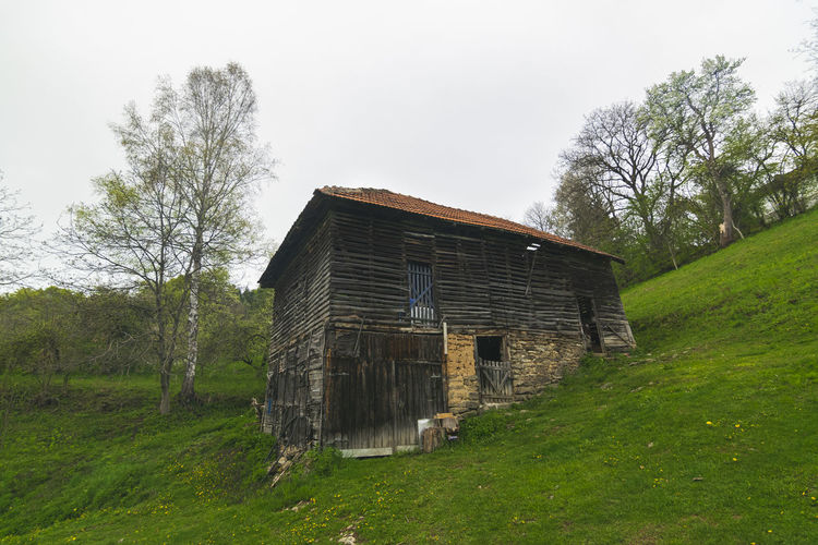Old abandoned house on field against sky