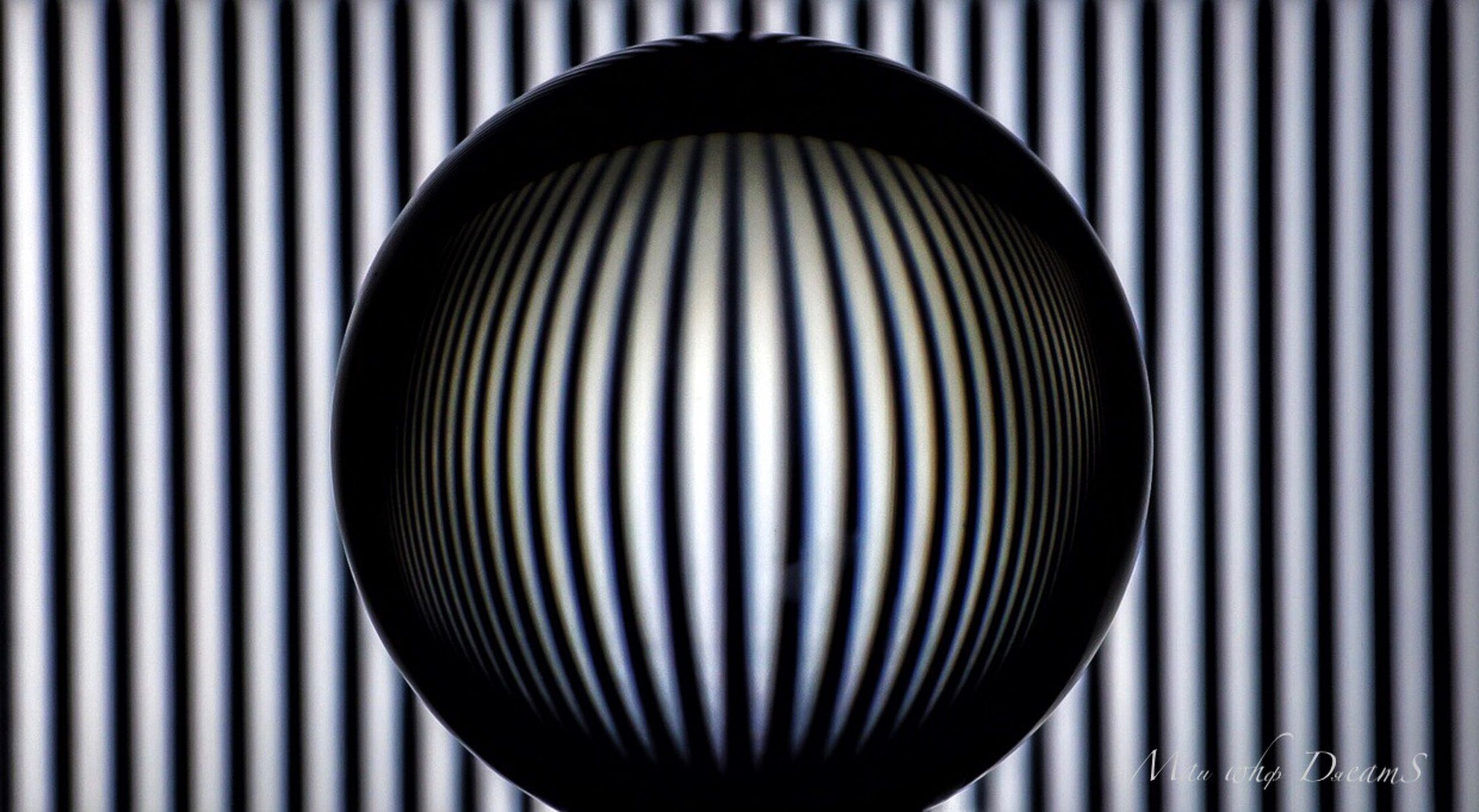 pattern, indoors, close-up, no people, geometric shape, shape, sphere, striped, lighting equipment, still life, design, circle, metal, single object, focus on foreground, abstract, illuminated, ball, electric light, shiny, light, electric lamp