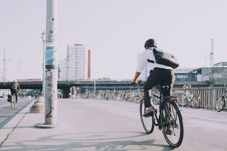 Rear view of man riding bicycle in city