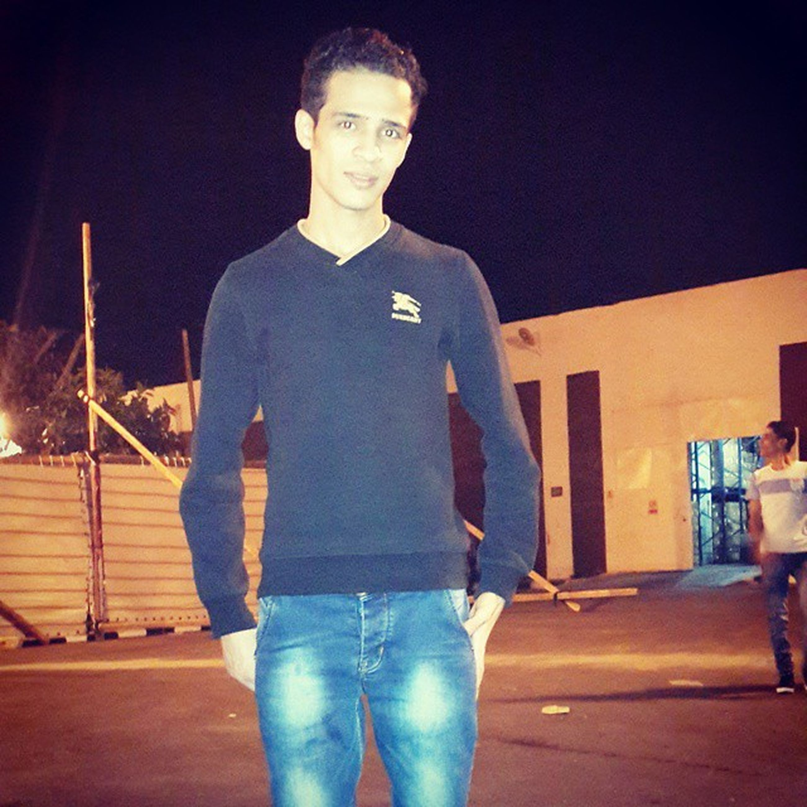 casual clothing, lifestyles, standing, young men, young adult, three quarter length, person, front view, leisure activity, full length, built structure, architecture, night, building exterior, looking at camera, portrait, communication, wall - building feature