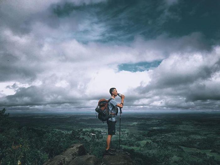 Full length of man standing on landscape against sky