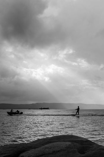 Silhouette man wakeboarding in sea against cloudy sky