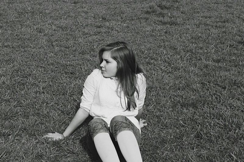 High angle view of woman sitting on grassy field at park