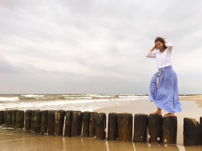 Low angle view of young woman standing on wooden posts in sea against sky