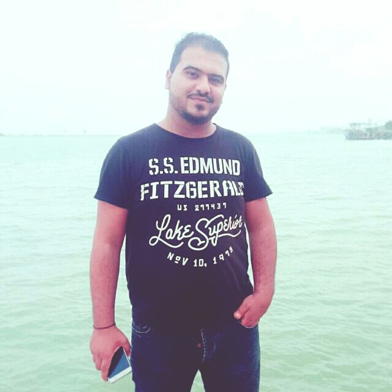 sea, one person, casual clothing, standing, looking at camera, t-shirt, outdoors, horizon over water, young men, real people, young adult, day, beard, portrait, nature, one man only, water, men, beauty in nature, sky, only men, adult, adults only, people