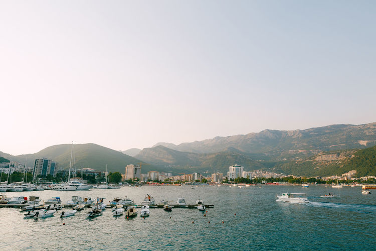Boats in marina against clear sky