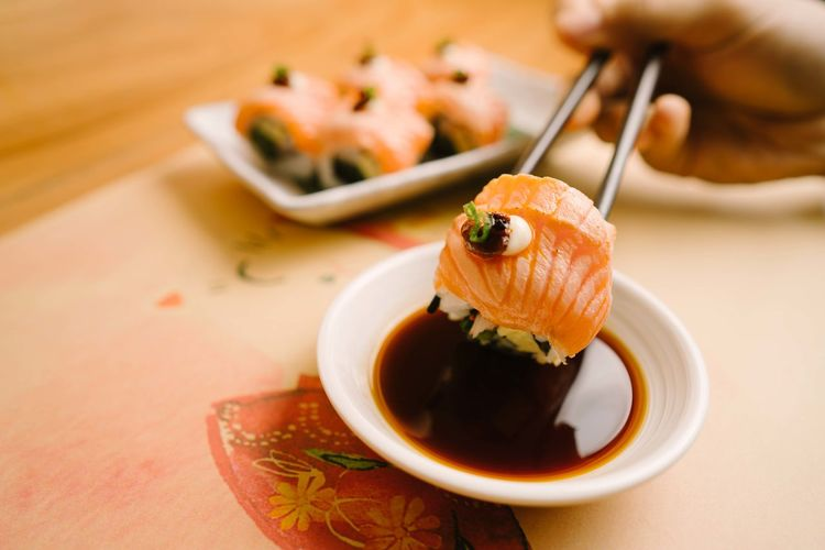 Sushi Food And Drink Food Asian Food Japanese Food Human Hand Sushi Seafood Human Body Part Chopsticks Hand Freshness Close-up Wellbeing Healthy Eating Focus On Foreground Rice Sauce Condiment Plate Soy Sauce Crockery Sashimi  Chinese Food Savory Sauce