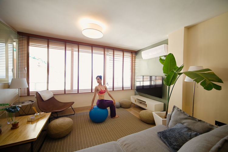 Woman exercising on fitness ball at home