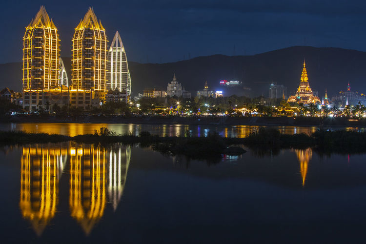 Reflection of illuminated buildings in city at night