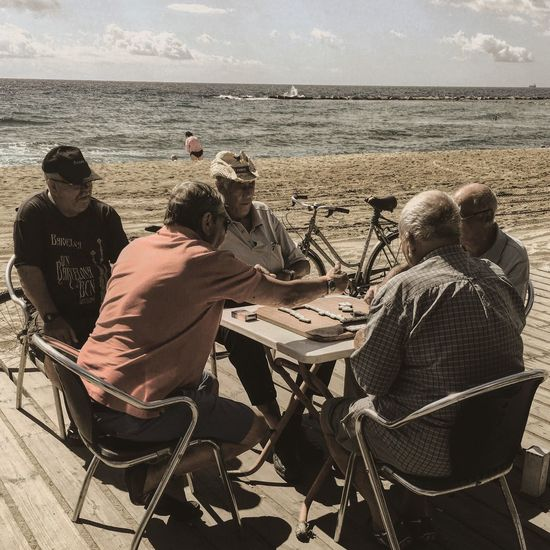 Sitting Water Leisure Activity Lifestyles Togetherness Casual Clothing Relaxation Vacations Tourism Holding Shore Tourist Sea Weekend Activities Sky Person Outdoors Cloud - Sky Old Oldpeople Backgammon Barcelona Barcelona, Spain Beach