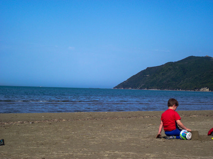 Boy Making Sandcastle While Sitting Against Sea At Beach