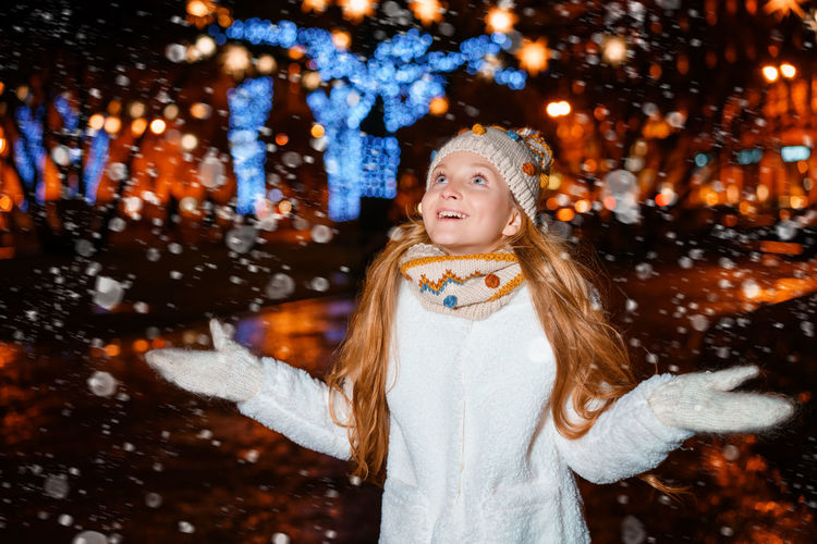 Portrait of girl standing on snow during christmas