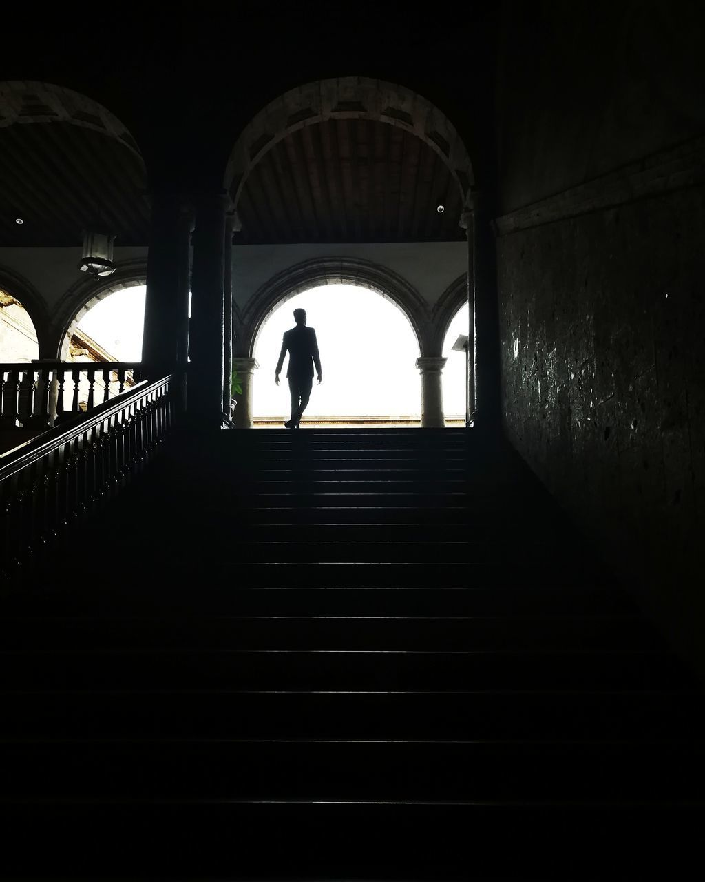 SILHOUETTE WOMAN STANDING ON STAIRCASE IN TUNNEL
