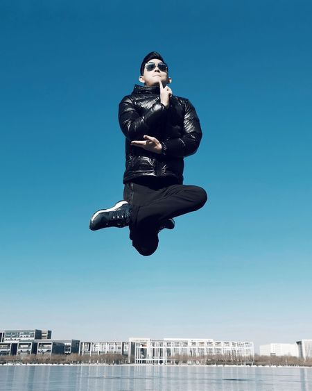 Man jumping against clear blue sky