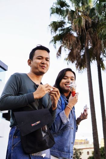Enjoy The New Normal Devouring Ice Cream Two People Young Adult Smiling City Adults Only Outdoors Adult Togetherness Happiness Real People People Eating Tree Alcohol Friendship Food Cheerful Men Sky Day EyeEm Best Shots