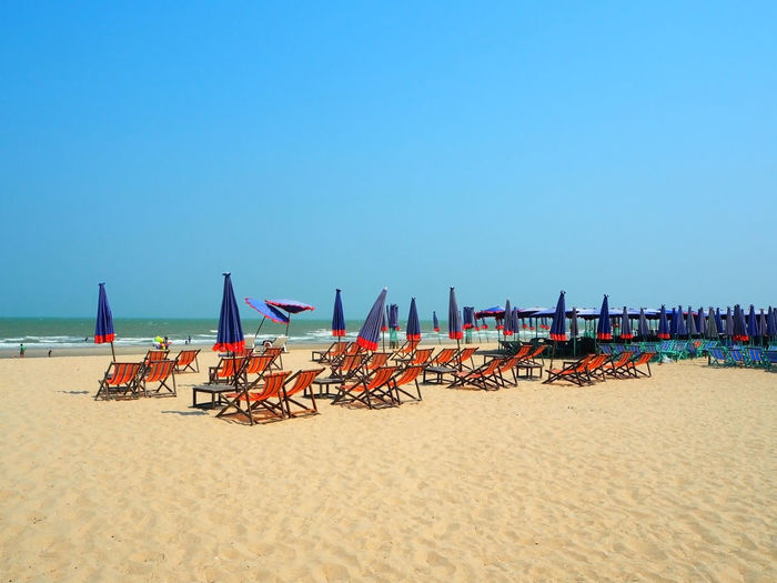 Deck Chairs And Parasols At Beach Against Clear Blue Sky