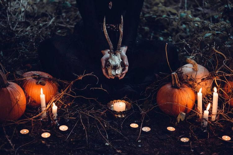 Low section of woman holding animal skull while sitting amidst pumpkins and burning candles during halloween